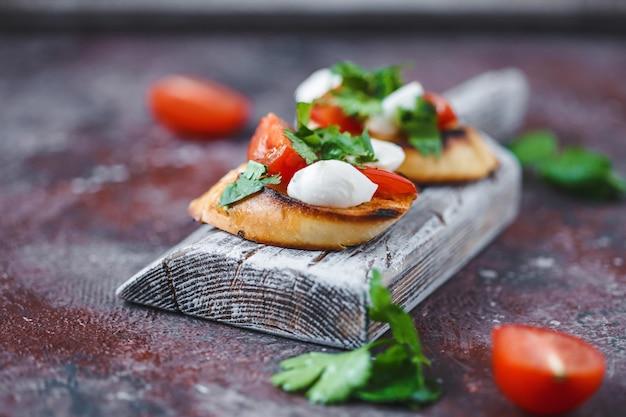 イタリアのブルスケッタ、トマト、モッツァレラチーズ、木の板にハーブ