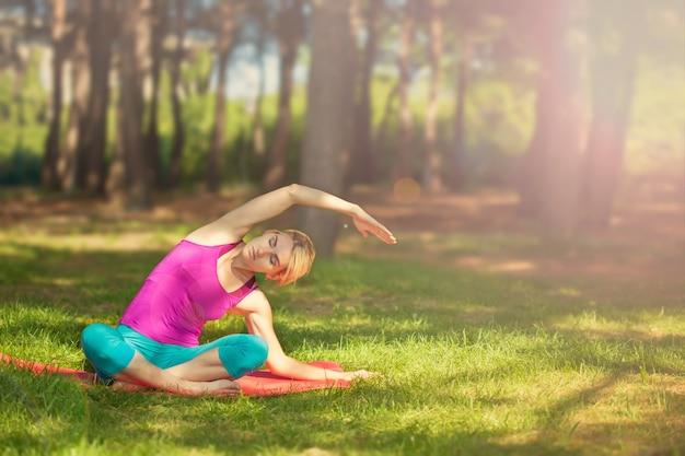 Девушка делает йогу на открытом воздухе в лесу. поддерживает здоровый образ жизни