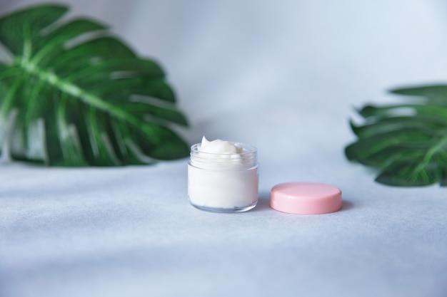 ヤシの葉の化粧品の瓶に自然な顔のクリーム。