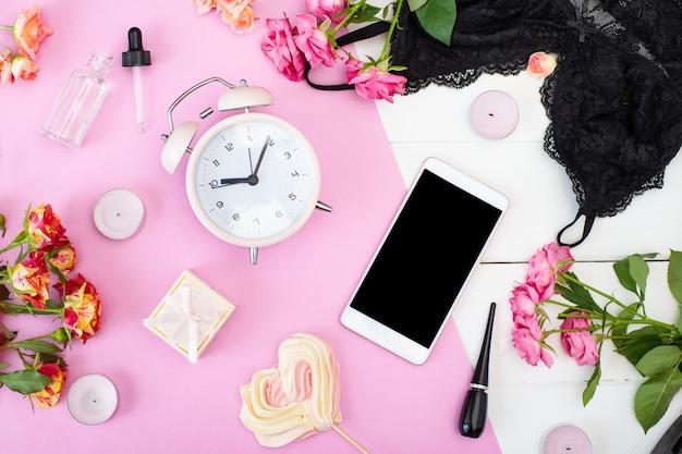 タブレット、目覚まし時計、下着、バラ、キャンドル、テーブルの上の化粧品