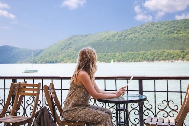 Путешественник блоггер девушка сидит в кафе и смотрит на красивое горное озеро