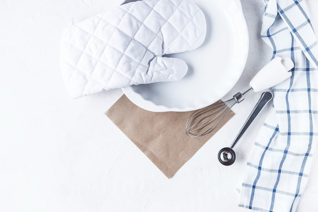 白い背景の上のキッチンテーブルの上で焼くための料理とキッチンアクセサリー