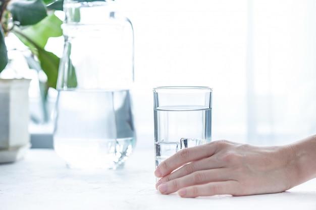 水と氷の白いテーブルの上のガラスカップ