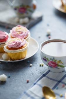 テーブルでの朝食。皿のケーキ、お茶、やかん、ミルクジャグ
