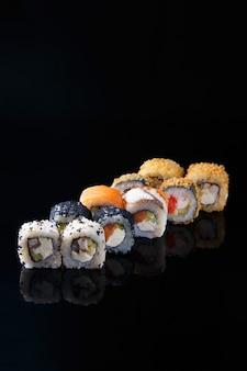Вкусный набор суши ролл с рыбой на черном фоне с отражением меню и ресторан