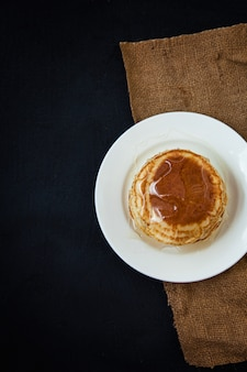 暗いテーブルの上に蜂蜜と食欲をそそるパンケーキ。メニュー、レストランのレシピ。提供しています。