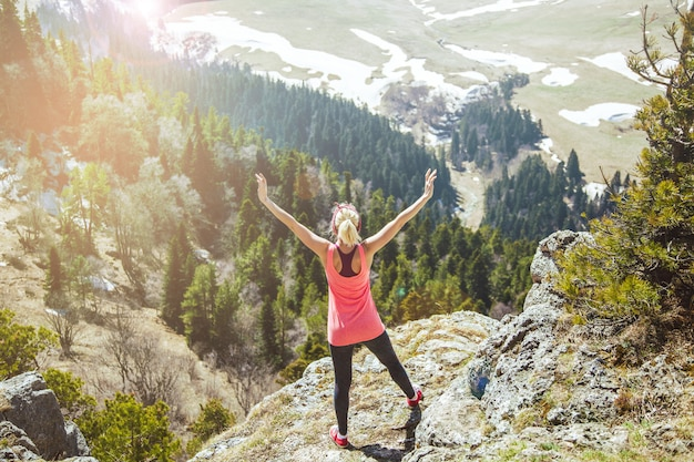 Молодая девушка путешественница стоит на вершине горы с распростертыми объятиями .. девушка любит путешествовать.