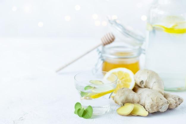 Здоровый имбирный напиток в чашке. корень имбиря, мед в банке, лимон на белом столе.
