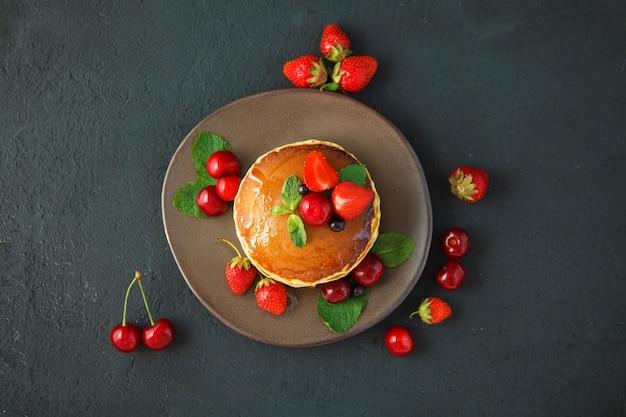 暗い黒の背景にイチゴ、ミント、蜂蜜、チェリーのプレートのパンケーキ。