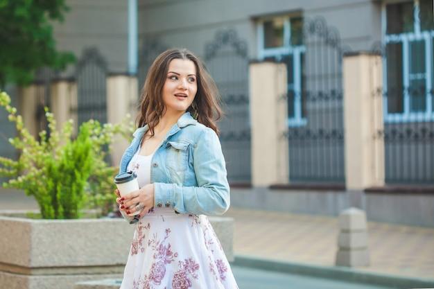 ジーンズのジャケットの美しいブルネットの少女は手でコーヒーを飲みながら街を歩く