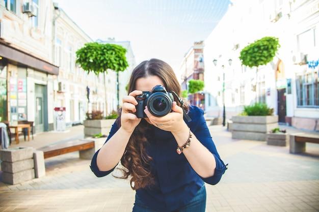 カメラで通りを歩いている美しい女性観光客と都市を探索するクローズアップを撮影しました。
