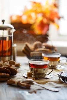 オレンジの葉の上のテーブルに暖かいお茶とカップ。居心地の良い、ホームコンセプト