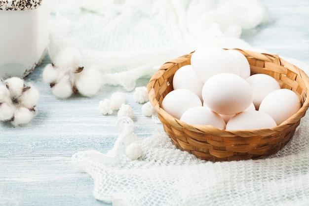 Белые пасхальные яйца в плетеной корзине на свет