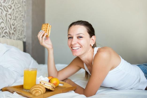 ベッドで朝食を食べて、笑顔の美しいブルネットの少女