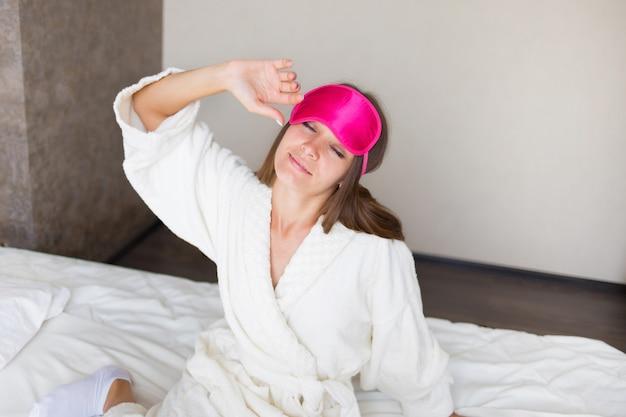 Красивая брюнетка девушка растягивается в постели в маске для сна