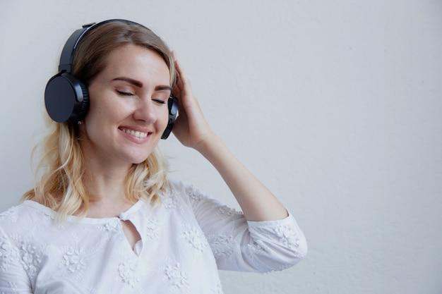 ヘッドフォンで美しいブロンドの女の子。彼女は音楽を聴いて楽しんでいます