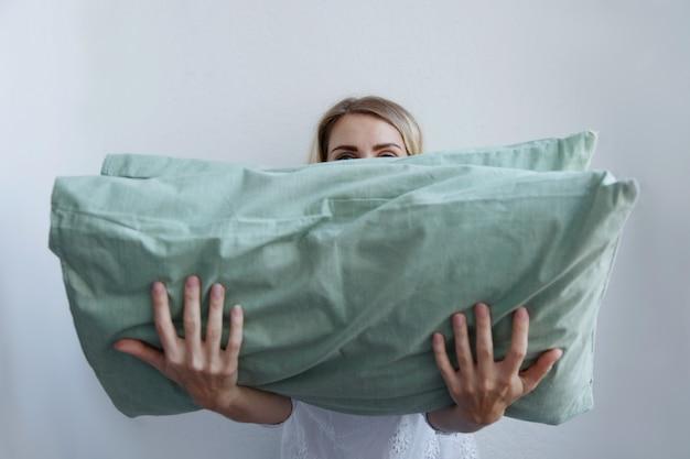 美しいブロンドの女の子は彼女の手でたくさんの枕を保持しています。彼女は喜んで彼らの上に横たわる