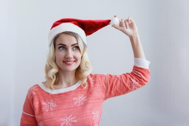 クリスマスと新年のコンセプト。新年のキャップ笑顔で美しい若いブロンドの女性。白い壁に