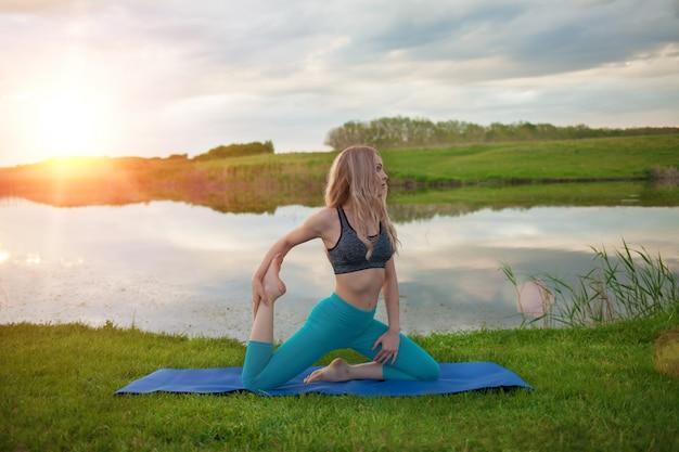 美しいブロンドの女の子は、夕暮れ時の湖でヨガを練習しています。閉じる