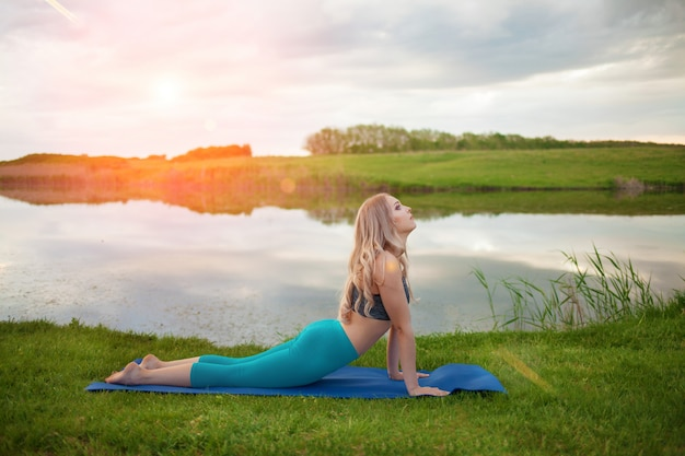 日没、クローズアップで湖でヨガの練習美しい運動ブロンドの女の子、それは健康的なライフスタイルをサポートしています