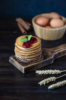 暗い木製のテーブルにミントとジャムのおいしいパンケーキ