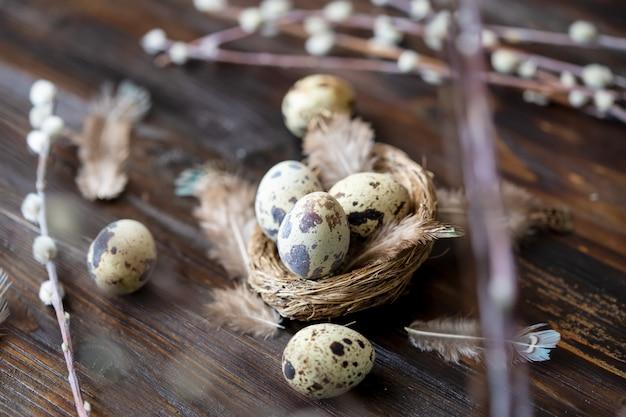 ウズラの卵、羽、木製のテーブルの上の柳の枝。ヴィンテージ効果