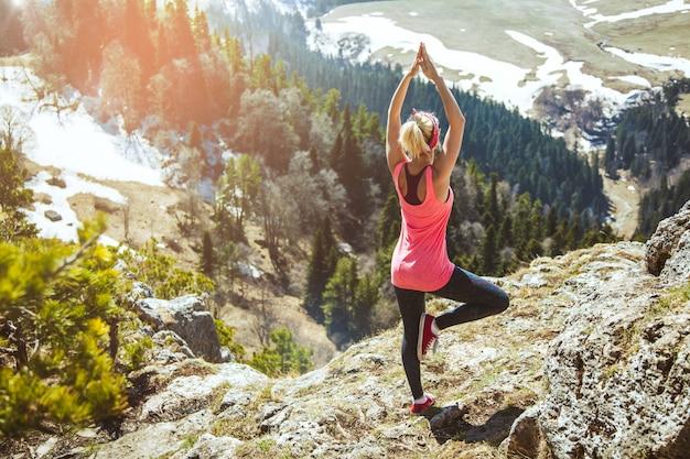 Молодая девушка путешественник сидит на вершине горы в позе йоги.