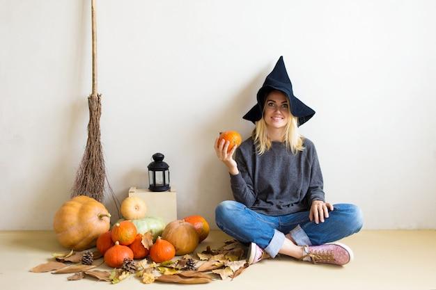 Красивая белокурая девушка в шляпе ведьмы с тыквами и метлой