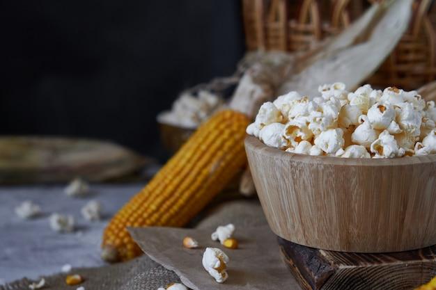 木製ボウルとテーブルの上のトウモロコシの伝統的なポップコーン。
