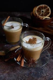 Две чашки горячего капучино с корицей и анисом на коричневой поверхности