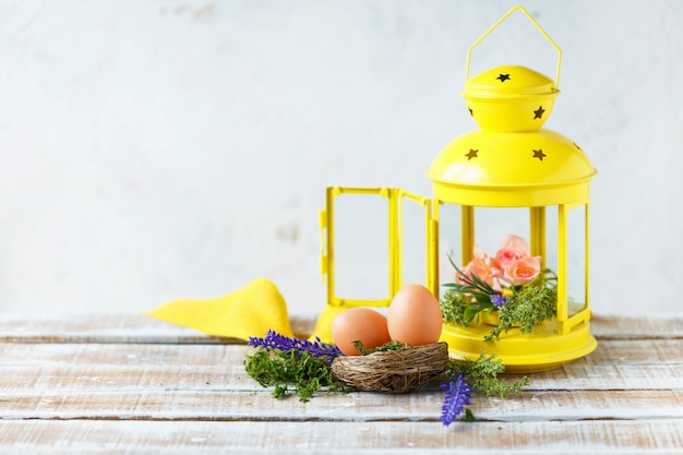 Яркие весенние цветы с пасхальными яйцами возле желтого декоративного фонаря