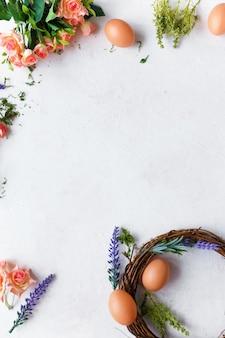 明るい春の花、灰色のイースターエッグと花輪