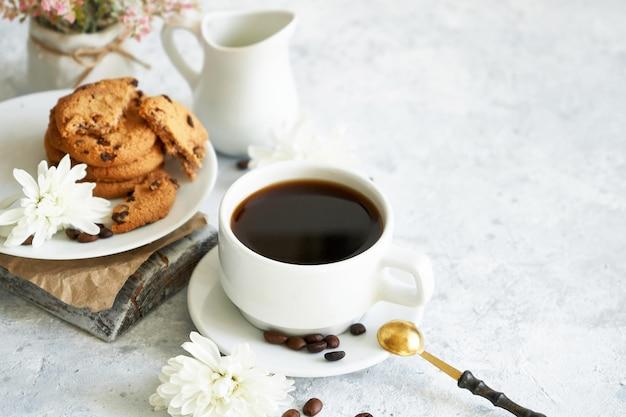 コーヒー豆とクッキーと黒の濃いコーヒーのカップ