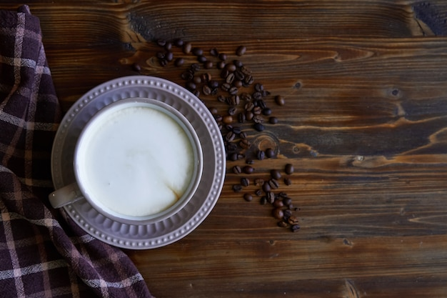 木製のコーヒー豆とカプチーノコーヒーのカップ