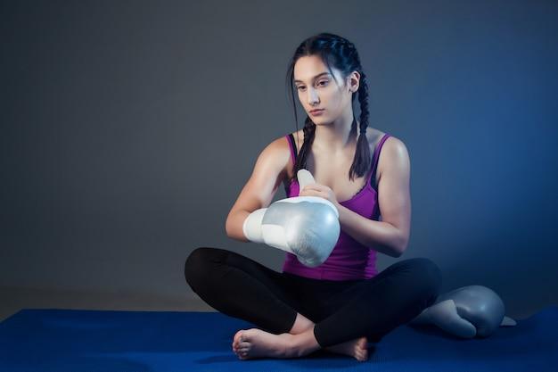 ボクサーの女の子がマットの上に座っている間ボクシンググローブを着て脱ぐ