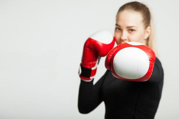 赤いボクシンググローブ、コピースペースを持つ白い背景を持つ少女