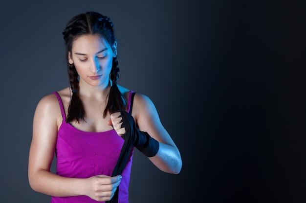 Женский боксер оборачивает руки черными боксерскими обертками