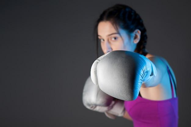 銀のボクシンググローブ、コピースペースと黒の背景を持つ少女