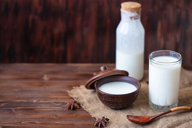 カップの自家製ヨーグルト、プロバイオティクスとケフィアのガラスプロバイオティクスの冷たい発酵乳製品飲料トレンディな食べ物と飲み物コピースペース素朴なスタイル。