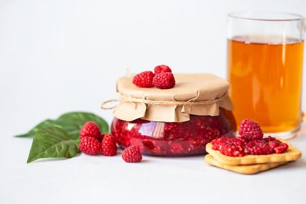 砂糖入りラズベリー、ヘルシーで新鮮なラズベリー、自家製ジャムの瓶入り、光の朝の朝食