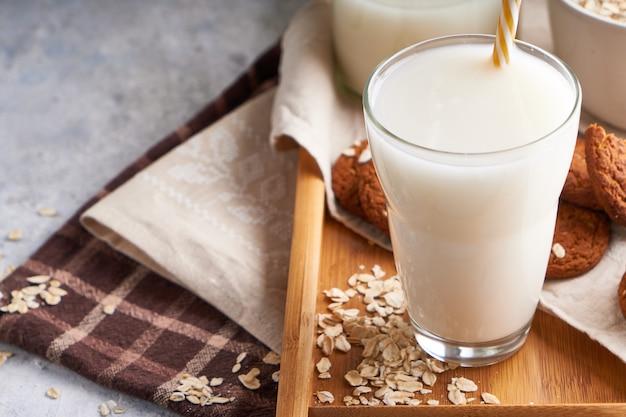 健康的な代替ミルク。ガラスとライトテーブルボトルの自家製オークミルクラクトースフリー