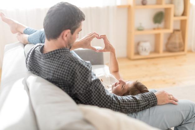 Вид сбоку влюбленная пара, отдыхая на диване и укладывая руки в сердце сердце знак дома