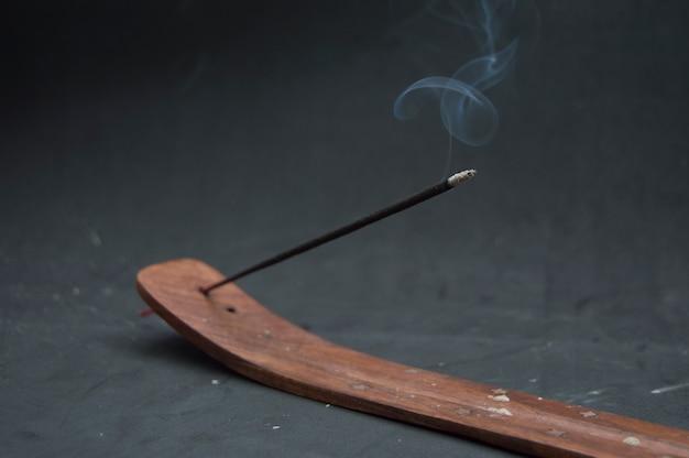 黒に煙で照らされた線香。