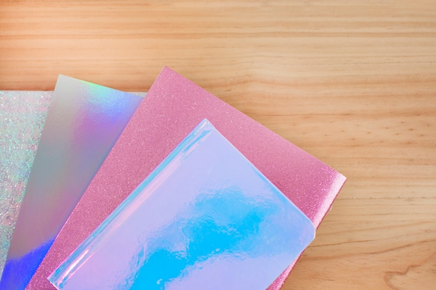 学校に戻るための木製の机の上にキラキラと色のノートブック虹色。