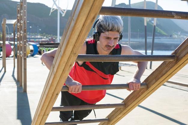 若い男の子が屋外ジムの木製の梁でスポーツを練習