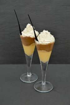 デザートに美しいグラスを添え、クリームとシナモンを添えて