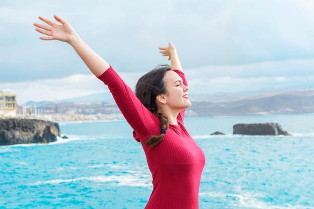 腕を空中に上げて、海を楽しんで幸せな女。