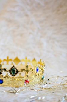 Золотая корона с цветными камнями на белом