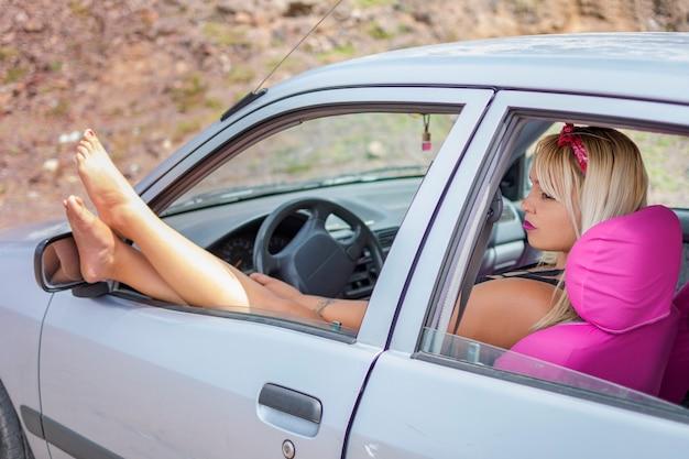 ドライバーの窓から足で休む彼女の車の中で美しい女性