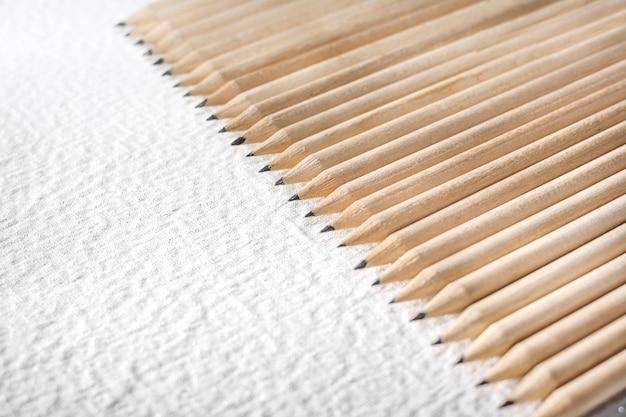 背景として白いテーブルに木製の鉛筆のグループ。